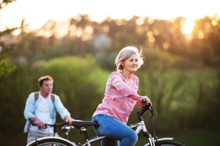 Beautiful senior couple with bicycles outside in spring nature cycling.