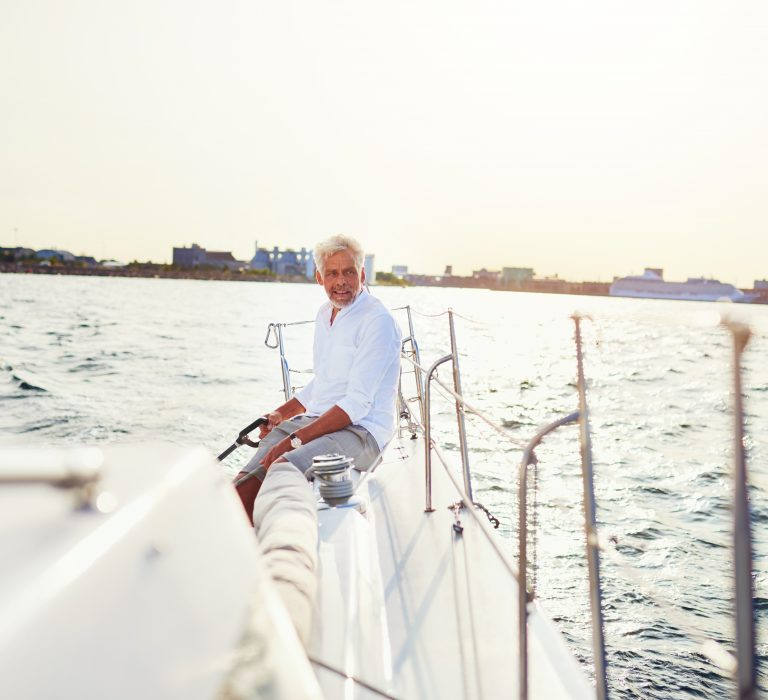 Mature man steering the rudder of his boat while out for a sail along the coast on a sunny day