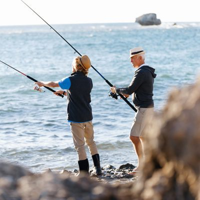 Senior man fishing with his teenage grandson at seaside
